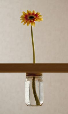 drill a hole in your table, attach jar underneath. place a single flower for minimalist perfection.