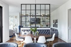 Eames Molded Plastic Chairs surround a Saarinen Oval Dining Table illuminated by a modern black chandelier and seating a black leather tufted dining bench beneath a steel and glass partition. #PlasticChair