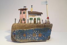Driftwood cottage sculpture with blue wave.