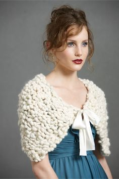 Like pale pebbles being washed by the waves, chunky knit wool shot through with flashes of silver forms Hand Knit by the Sea's soft and dimensional wrap. Tie and hook-n-eye closure. Wool, satin. Dry c