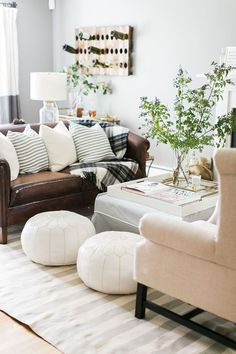 Cozy living room with white Moroccan poofs, a blush pink chair and a brown leather couch. Brown Leather Couch Living Room, Living Room Sofa, Dark Brown Leather Sofa, Living Room Decor Brown Leather Couch, Brown Couch Pillows, Brown Leather Furniture, Dark Sofa, Living Room Decor Ideas Brown Sofa, Living Room With Brown Couches