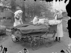 Wounded soldiers in invalid chairs being taken round the grounds of the 4th London General Hospital, WW1