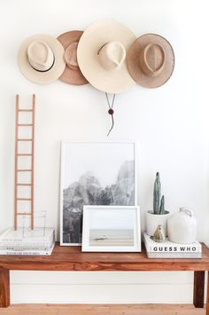Bright minimalist space with a wood coffee table, an indoor cactus, and a wall decorated with hats