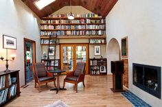 The living room's vaulted ceiling made space for a library with open shelving and a custom sliding ladder