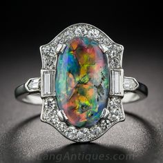 Platinum Black Opal and Diamond Art Deco Ring. A magnificent and mesmerizing Lightening Ridge black opal, shimmers and glows a complete palette of electric colors, fills the center of this chic, Art Deco ring. This enchanting jewel is finely handcrafted in platinum, circa 1925, and is set with a sparkling array of small round, baguette and bullet-shape diamonds