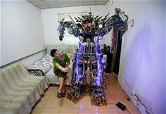 """Tao Xiangli controls his self-made humanoid robot with a remote controller as he poses with it at his Beijing home. The self-taught Chinese inventor built the home-made robot, named """"The King of Innovation"""", out of scrap metal and electronic wires that he bought from a second-hand market."""