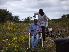 Imigrante sudanês recebe um corte de cabelo em um acampamento situado perto de Calais, norte da França - 06/08/2015