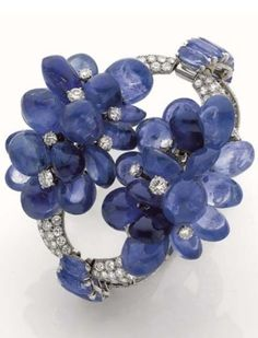 A magnificent Art Moderne diamond and sapphire bracelet, by Cartier, circa 1939. The hinged bracelet set with diamonds, decorated with two clusters of articulated cabochon sapphire grapes studded with diamonds, the fasteners set with cushion sapphires, mounted in platinum and white gold. Unsigned. #Cartier #ArtModerne #bracelet