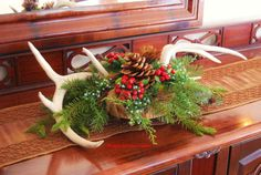 Deck your halls with this woodland inspired Christmas centerpiece . An unusual addition to your holiday festivities this natural and woodsy feeling centerpiece will complete your seasonal decorations with its true nature inspired look .This arrangement features two genuine deer antlers attached to a beautiful rustic vintage wood bowl . The bowl holds a bountiful selection of natural and very realistic faux juniper and pine greens , red berries , real pinecones , real pheasant feathers , and…