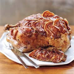 Pancetta-Wrapped Roasted Turkey | After rubbing this turkey with a bold and delicious mix of chile powder, cumin, sugar and herbs, Tim Love blankets it with slices of salty, fatty pancetta, resulting in a supermoist and savory bird.