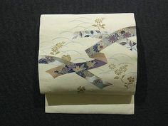 This is a Hige Tsumugi Nagoya obi with a design of 'kiku'(chrysanthemum), 'sakura'(cherry blossom), 'hagi'(Japanese bush clover) and 'kaede'(maple leaf) on 'noshi'(gift wrapping paper), which is dyed