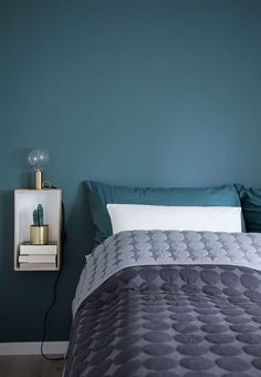 Warm green coloured wall creates cosiness and a nice atmosphere in the bedroom. The bedding is matched with the nice green colour.