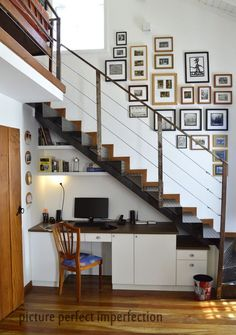 Local craftsmen executed our design for a custom-fitted office under the stairs leading to the mezzanine. #homeoffice #stairs #gallerywall