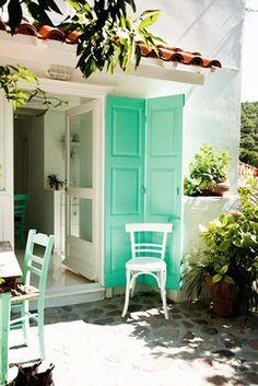 stone patio with white glass door and solid wood green door.