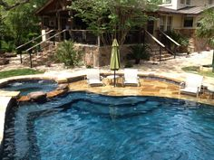 Stone Baja Shelf Entry. Pool level spa with stone spillway. Barbados Blue Quartzscapes Plaster.