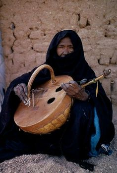 Niger, Tribal Music, Tuareg Woman Playing An Imzad. Traditional Instrument Consisting Of A Goatskin Covered Gourd Or Wooden Resonator Played With A Curved Bow And Horsehair String. Pub Radio, Afrique Art, Kalimba, African Culture, World Music, Horse Hair, Sound Of Music, Music Stuff, Mandolin