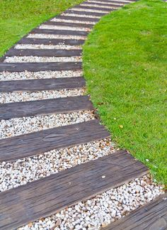 This curved walkway is comprised of alternating weathered wood and white pebble segments.
