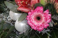 Arrangiert mit silbernen Weihnachtskugeln und Engelshaar präsentiert sich die pinke Gerbera!