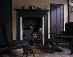 The fireside in the living room of the 1930s house showing the range, mantlepiece, and two easy leather armchairs, in one of the Birmingham back to backs.
