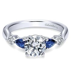 The elegance of a vintage ring with a contemporary flair. This straight styled engagement ring is adorned with diamond and sapphire side stones to highlight your flawless center stone. .10tcw, Interch