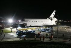 Crews look on as space shuttle Endeavour leaves Los Angeles International Airport and is transported on city streets to the California Science Center in Los Angeles, California October 12, 2012.