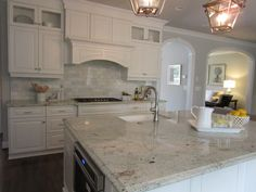 White kitchen, dark wood floors, marble backsplash, colonial white granite