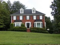 beautiful red brick house with black shutters and white trim