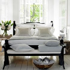 For a timeless look that's perfect for summer, go for a coastal-inspired scheme. White shutters, crisp neutral bedlinen and painted floorboards evoke a feeling of lazy days and warm summer nights.