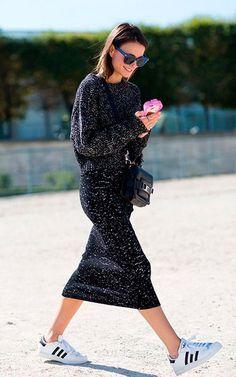 Street style look com blusão, saia midi e tênis.