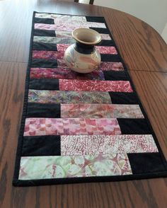 mug art A modern batik patchwork table runner in black with a lovely mix of batik fabric strips in pinks, greens, creams and burgundy, perfect for adding a touch of class to your dining table Patchwork Table Runner, Table Runner And Placemats, Table Runner Pattern, Quilted Table Runners, Modern Table Runners, Christmas Party Table, Christmas Table Decorations, Black Pink, Pink And Green