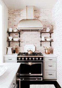 copper and black accents with exposed brick - so pretty in the kitchen