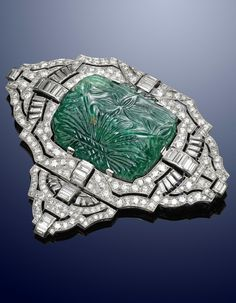 An Art Deco white gold, diamond and carved emerald brooch. Set with a large emerald carved to both sides with foliate decoration, millegrain set throughout with circular and baguette shaped diamonds, mounted in white gold. The emerald is 3.5cm wide and the brooch 8cm wide. #ArtDeco #brooch