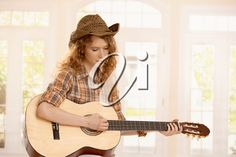Attractive girl playing on guitar, dressed in country style.