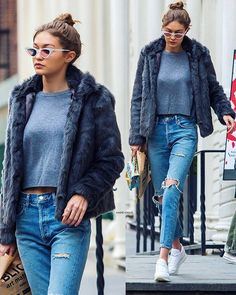 Gigi Hadid's casual style - ripped skinny jeans, white sneakers, grey crop top, fur jacket, and messy bun + cat eye glasses