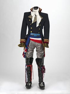 """This is one of Adam Ant's performance costumes known as the """"Prince Charming"""" costume. The costume was made in 1981 and is housed at the Victoria and Albert Museum. The costume was made by Adam Ant, Charles Davis Whiteing, Yvonne Swinden, and David Lewis. The military jacket is made of wool, satin, furnishing fabric, gold braid and metal buttons."""