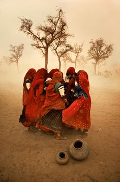 This picture is of women singing and praying, battered by sand and dust, Dust storm in Rajasthan, India.