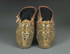 A PAIR OF EASTERN WOODLANDS QUILLED HIDE MOCCASINS  of front seam construction, with verticle side seams and eyelet lacing, stitched with orange, black and white porcupine quills, each decorated with three verticle bands down the front and a curvilinear element on the heel, trimmed with painted red hide, separate soles
