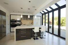 Peppe This modern kitchen extension by Apropos incorporates three sets of folding sliding doors with Conservatory Kitchen, Conservatory Design, Conservatory Extension, Kitchen Orangery, Kitchen Diner Extension, Open Plan Kitchen, Kitchen Layout, Glass Extension, Extension Ideas