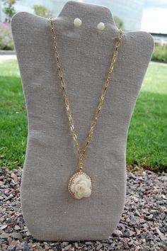 Set de collar largo dorado con dije en forma de flor con resina color beige y aretes a juego $210.00