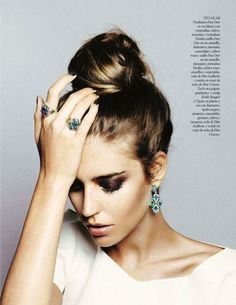 high bun accentuated with dangle earrings and dark eye shadow