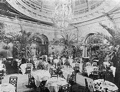 """WALDORF-ASTORIA """"PALM GARDEN IN 1902"""". In 1900, Harper's Bazaar described the Waldorf-Astoria as """"the fashion of New York and the Mecca of visitors...here is the chosen gathering place of New York society, which comes here to see and to be observed..."""""""
