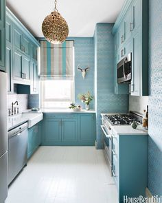 Her New York City kitchen may be on the small side, but designer Sheila Bridges didn't let that cramp her style. An elegant silvery-blue wallpaper adds some unexpected excitement to a tiny space.    - HouseBeautiful.com