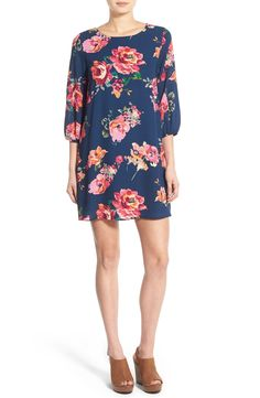 Vivid flowers pop on the blue background of this feminine shift dress. Pairing this with wedges or sandals depending on the occasion.