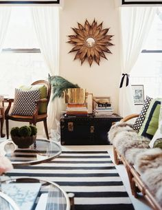 love the white background with strong pops of pattern and a natural element (sunburst mirror)