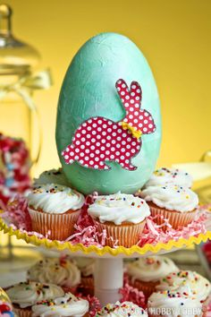 This adorable DIY egg is découpaged with aqua-blue tissue paper, embellished with a polka-dotted and glittered bunny, and hot glued into place on a cake stand.