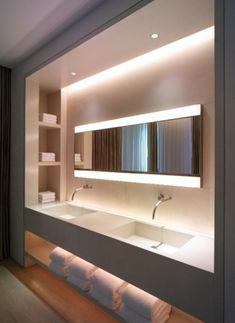 A Custom Built Wall Mounted Vanity Unit With Cove Lighting Shelf Niches And A Long Expanse Of Poured Sink And Counter Offers A Boutique Hotel Feel At Home