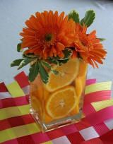Orange gerbera daisies and orange slices center piece.