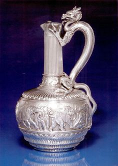 """AN AMERICAN SILVER """"JAPANESE STYLE"""" EWER, TIFFANY & CO., NEW YORK, CIRCA 1883 of bottle form, the lower body chases with spirals below a band of frolicking elephants before chased foliage, gadrooned shoulders topped by a band of ducks in relief, reeded neck & pulled-out spout, the handle formed by a finely modeled figure of a whiskered dragon wigh haffy legs & spalyd claws, the base with 1883 presentation inscription, marked on base & numbered 7366-6410 / 1047. 64oz, height 14 in."""