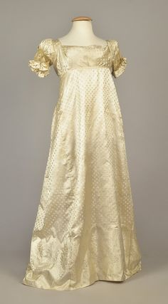 ENGLISH DAMASK GOWN with FLORAL BORDER, c. 1810 White satin figured with floral devices, having empire bodice with square neck and short sleeve inset with floral lace above a double ruffle, two back ties, wide A-line skirt patterned with floral sprigs and swags. B-34, high W-30, L-50. (Several minor spots, light watermarks).
