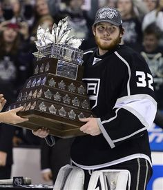 Los Angeles Kings goalie Jonathan Quick carries the Conn Smythe trophy as the most valuable player after the Kings beat the New Jersey Devils 6-1 to win the Stanley Cup during Game 6 of the NHL hockey...